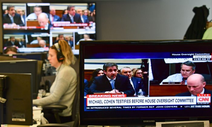 View of television screens inside a newsroom as they air live Michael Cohen's testimony before the House Oversight and Reform Committee on Feb. 27, 2019. (EVA HAMBACH/AFP/Getty Images)