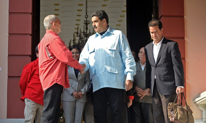 Venezuelan regime leader Nicolas Maduro (C) shakes hands with Eliecer Herlinton Chamorro Acosta, a leader of the leftist guerrilla group ELN, at the end of a meeting with a negotiator of the Colombian government, Frank Pearl (R), in Caracas, Venezuela, on March 30, 2016. (Federico Parra/AFP/Getty Images)