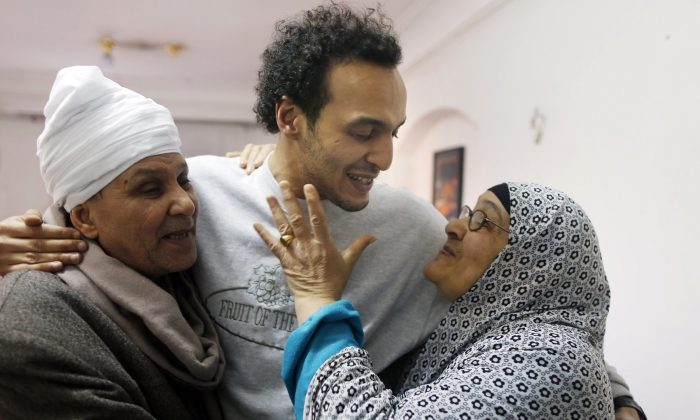 Mahmoud Abu Zaid, center, a photojournalist known as Shawkan, is hugged by his parents at his home in Cairo, Egypt, on March 4, 2019. (Amor Nabil/AP Photo)