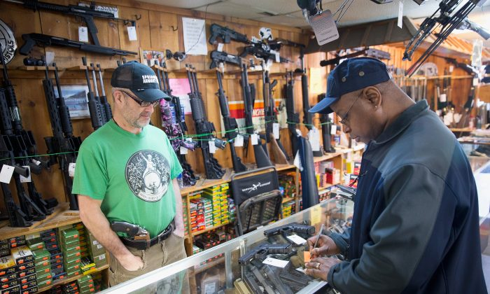 Danny Egan (L) helps a customer shop for a handgun at Freddie Bear Sports on March 11, 2015 in Tinley Park, Illinois. Scott Olson/Getty Images