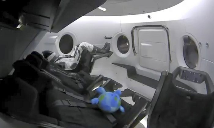 A life-size test dummy along with a toy floats in the Dragon capsule as the capsule made orbit on March 2, 2019. (SpaceX via AP)
