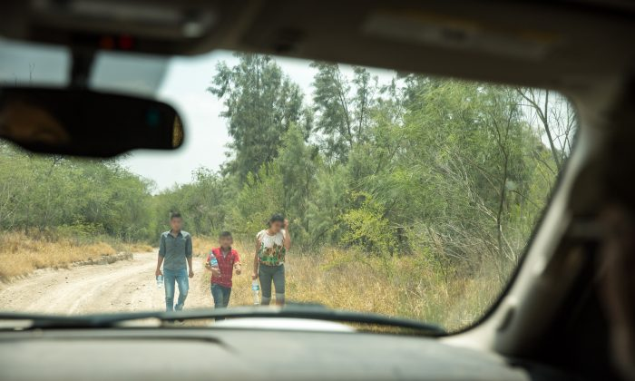 A group of unaccompanied minors seeks out Border Patrol after illegally crossing the Rio Grande from Mexico into the United States in Hidalgo County, Texas, on May 26, 2017. (Benjamin Chasteen/The Epoch Times)