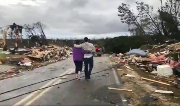 People walk amid debris in Lee County, Ala.