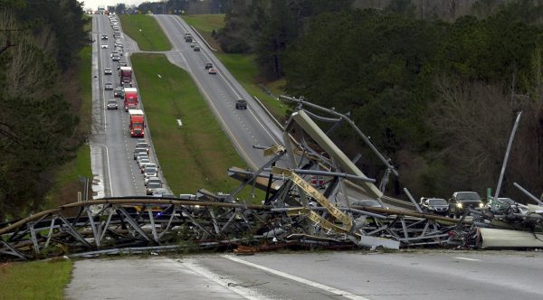 A fallen cell tower lies across U.S. Route 280 highway in Lee County