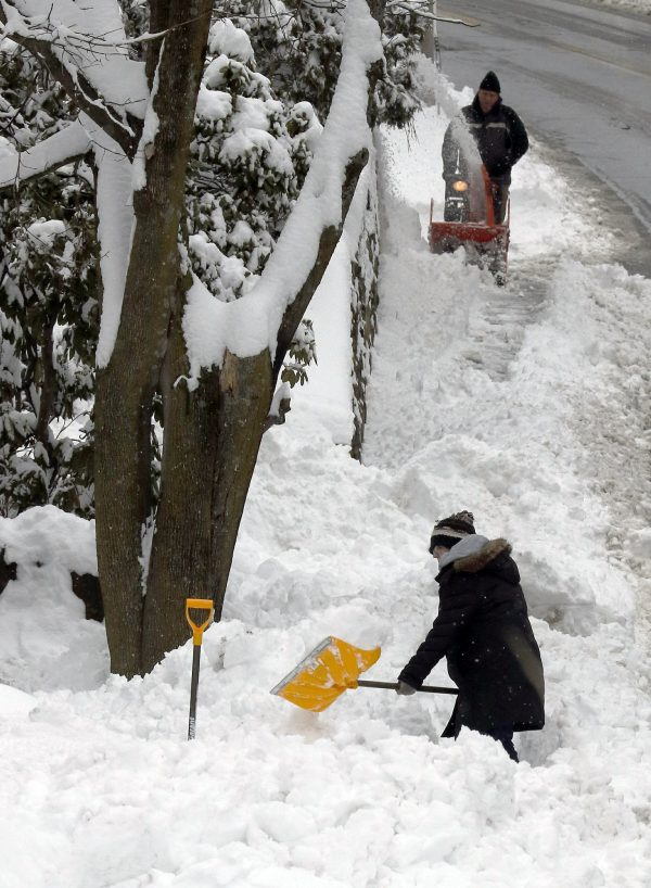 Residents clear snow after an overnight snowstorm dropped nearly a foot of snow