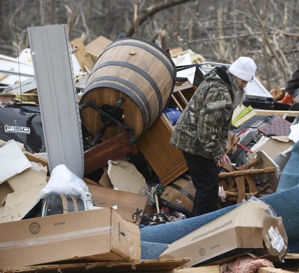 a woman looks through the debris of her home