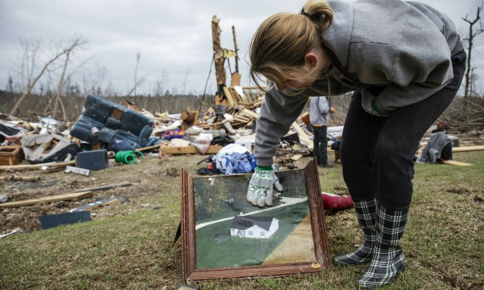 Debris from a friend's home stands in the background as Ashley Griggs wipes away dirt from a photo found in the rubble of what it used to look like before it was destroyed by a tornado in Beauregard, Ala., on March 4, 2019. (David Goldman/AP Photo)