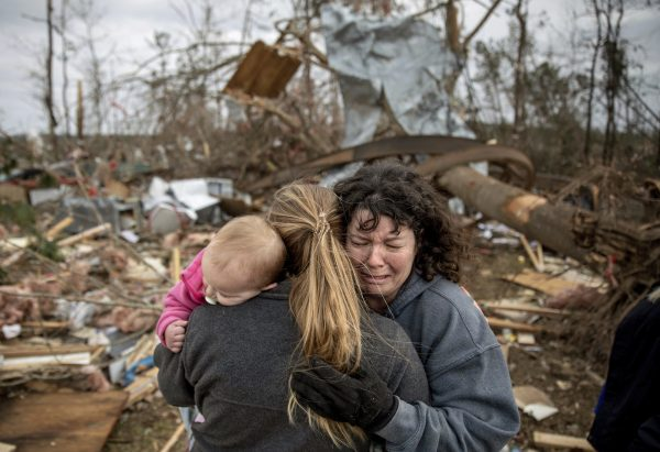 a woman is comforted after losing loved one in tornado