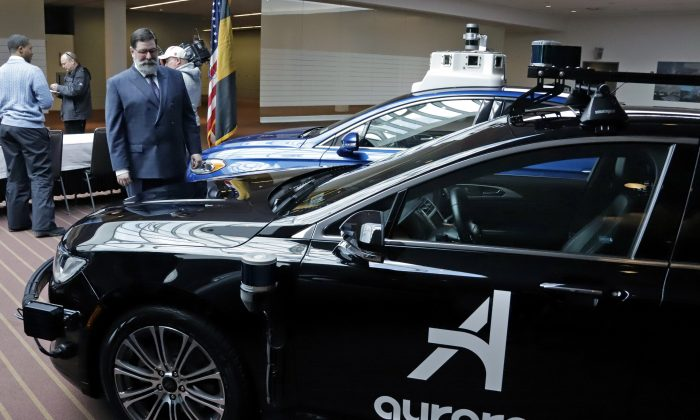 Pittsburgh Mayor William Peduto, left, checks out autonomous vehicles designed by Aurora Innovations in Pittsburgh, Mar. 4, 2019. (Gene J. Puskar/AP)