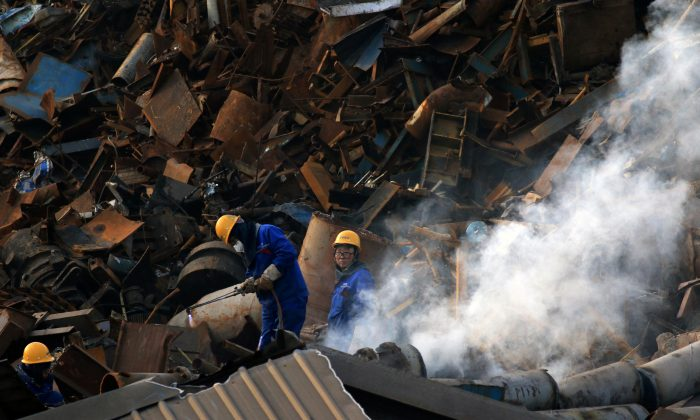 Workers dismantle scrap metal at a steel plant in Huaian, Jiangsu Province, China on March 4, 2019. (Reuters)
