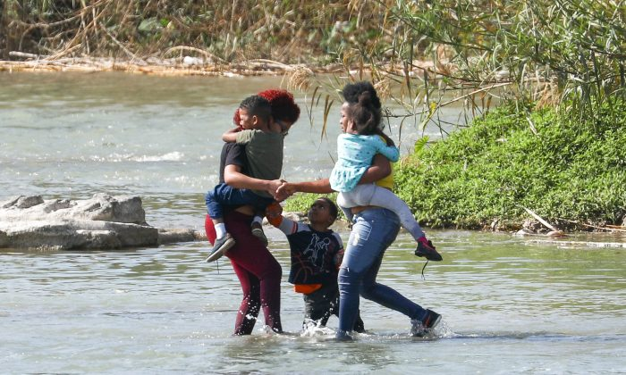 Two women and three children attempt to cross the Rio Grande from Mexico into the United States illegally near Eagle Pass, Texas, on Feb. 16, 2019. (Charlotte Cuthbertson/The Epoch Times)