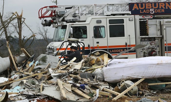 Rescue workers in a four-wheeler pass by the wreckage of a home along Lee Road 38 after a March 3 tornado tore through Beauregard, Ala., on March 4, 2019.(Curtis Compton/Atlanta Journal-Constitution via AP)