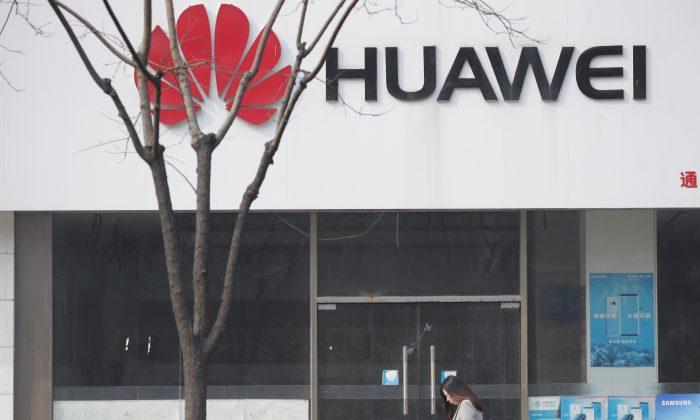 A woman walks past a Huawei store in Beijing on March 2, 2019. (Jason Lee/Reuters)