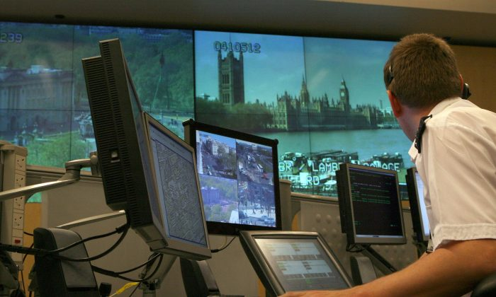 A police officer watches banks of television monitors in London on April 20, 2007.  (Matt Cardy/Getty Images)