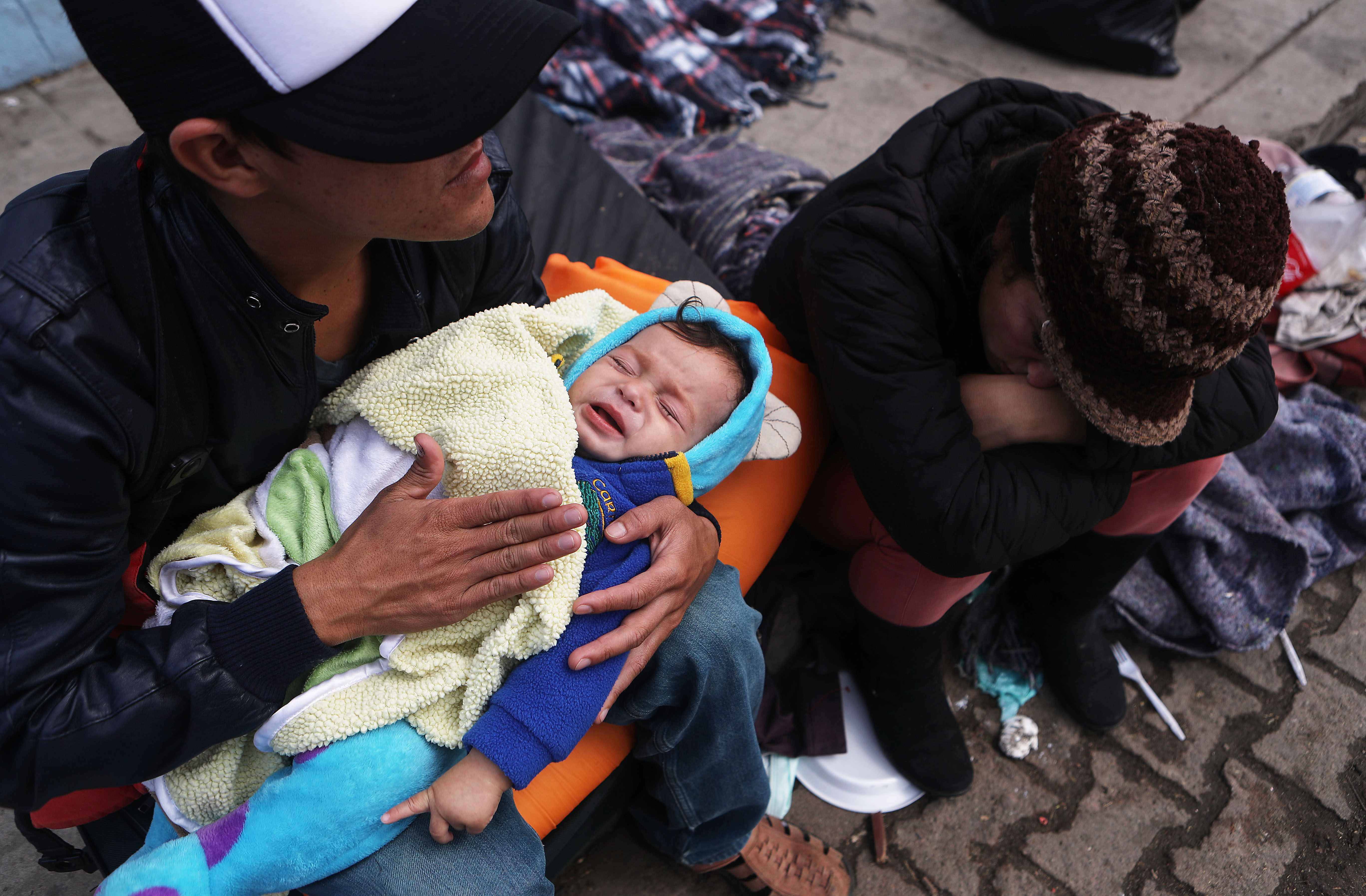 Honduran father Alexandre holds his son Karmaliel, who is sick with a fever