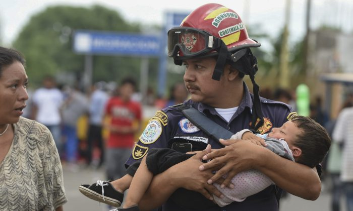 A Guatemalan firefighter carries an ailing baby, as an Honduran migrant caravan heading to the US, reaches the Guatemala-Mexico international bridge in Tecun Uman, Guatemala on Oct. 19, 2018. (ORLANDO SIERRA/AFP/Getty Images)