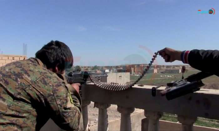 FILE PHOTO: A soldier said to be from US.-backed Syrian Democratic Forces is seen firing a rifle from a rooftop towards IS targets in Baghouz, Syria, in this screen grab taken from video said to be shot March 4, 2019, and uploaded to social media website on March 5, 2019. Social Media Website/ via REUTERS