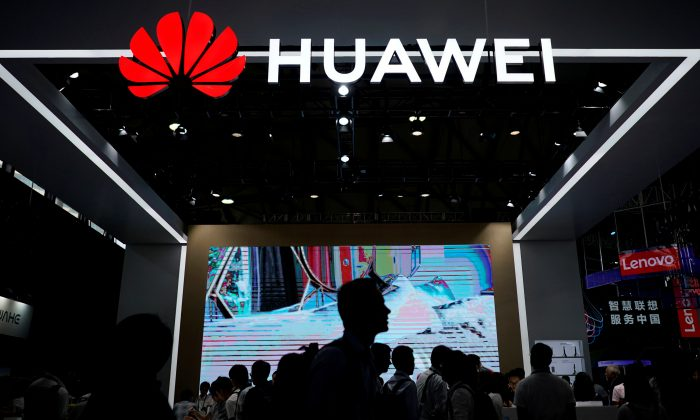 People walk past a sign board of Huawei at CES (Consumer Electronics Show) Asia 2018 in Shanghai, China Jun. 14, 2018. (Aly Song/Reuters)