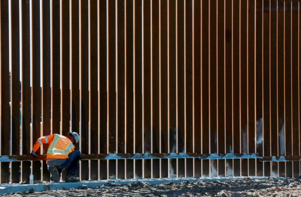 Construction workers build a secondary border wall