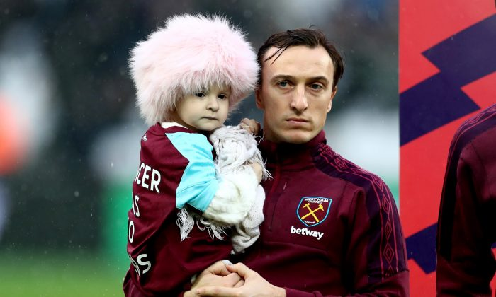 Mark Noble of West Ham United holds Isla Caton as he lines up prior to the Premier League match between West Ham United and AFC Bournemouth at London Stadium in London, UK, on Jan. 20, 2018. (Catherine Ivill/Getty Images)