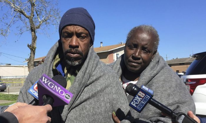 Emmett Rhodes, left, and neighbor Willie Tyson stand outside a house where authorities found a woman and two children killed and another woman and child critically injured in Terrytown, La., on March 6, 2019. (Kevin McGill/AP Photo)