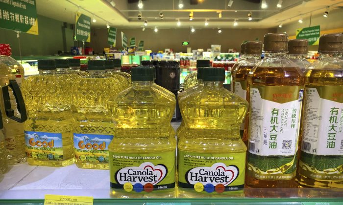 Bottles of Canola Harvest brand canola oil, manufactured by Canadian agribusiness firm Richardson International, are seen on the shelf of a grocery store in Beijing on March 6, 2019. One of Canada's largest grain processors said on March 5 that China has revoked its permit to export canola there, a move that some saw as retaliation for the Canadian government's arrest of a top executive for the Chinese tech giant Huawei. (Mark Schiefelbein/AP)