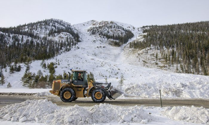 Crews work to remove the snow debris from a controlled avalanche that spilled onto Interstate 70 near Loveland Pass, Colo., on March 5, 2019. (Hugh Carey/Summit Daaily News via AP, File)