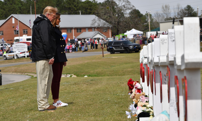 President Donald Trump and First Lady Melania Trump stand before a row of crosses honoring 23 people who died in the storm outside Providence Baptist Church in Opelika, Alabama, on March 8, 2019, during a tour of tornado-damaged areas in the southern US state. (Nicholas Kamm/AFP/Getty Images)