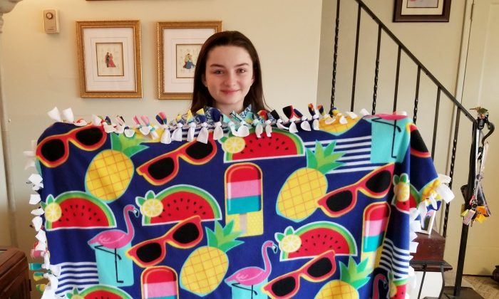 Meredith Kass, a senior at Kellenberg Memorial High School in Uniondale, N.Y., holds a Meredith's Favorite Blanket to help those in need. (Photo by Rolyne Joseph)
