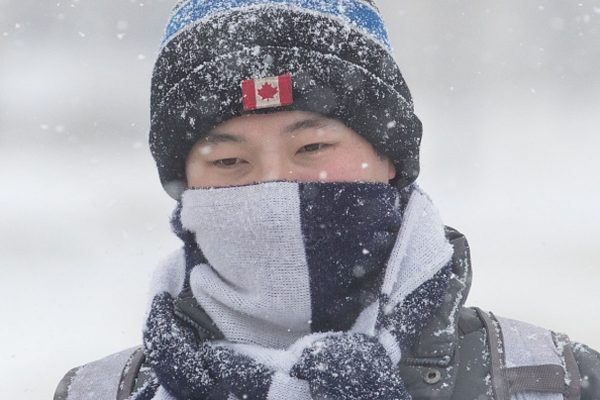 Snow lands on a person's hat as snow falls in Kingston,