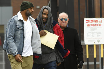 Singer R. Kelly center, walks with his attorney Steve Greenberg