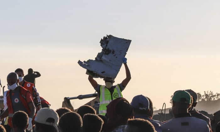 "A man carries a piece of debris on his head at the crash site of a Nairobi-bound Ethiopian Airlines flight near Bishoftu, a town some 60 kilometres southeast of Addis Ababa, Ethiopia, on March 10, 2019. - A Nairobi-bound Ethiopian Airlines Boeing crashed minutes after takeoff from Addis Ababa on March 10, killing all eight crew and 149 passengers on board, including tourists, business travellers, and ""at least a dozen"" UN staff. (Photo by Michael TEWELDE / AFP)        (Photo credit should read MICHAEL TEWELDE/AFP/Getty Images)"