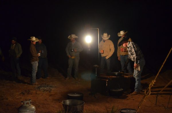 Cowboys drinking coffee at camp before dawn 3