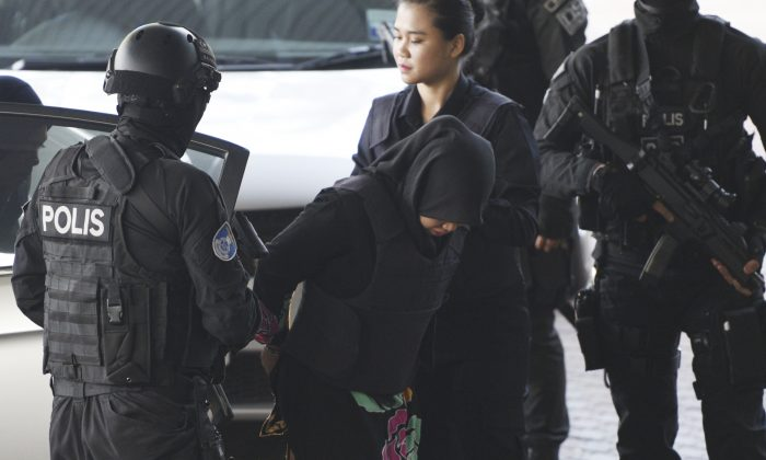 Indonesian Siti Aisyah, center, is escorted by police as she arrives at Shah Alam High Court in Shah Alam, Malaysia, on March 11, 2019. (Yam G-Jun/AP Photo)