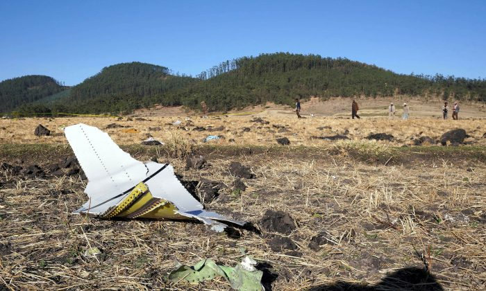 A piece of the fuselage of ET Flight 302 can be seen in the foreground as local residents collect debris at the scene where Ethiopian Airlines Flight 302 crashed in a wheat field just outside the town of Bishoftu, 62 kilometers southeast of Addis Ababa in Addis Ababa, Ethiopia on Mar. 10, 2019.