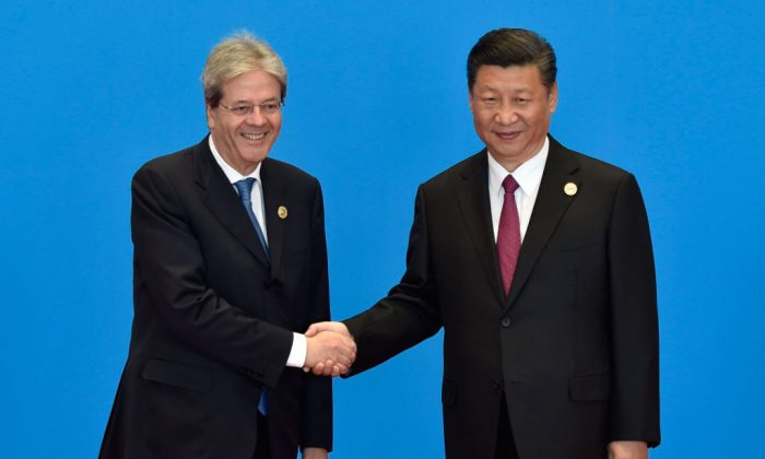Former Italy's Prime Minister Paolo Gentiloni (L) shakes hands with Chinese leader Xi Jinping during the welcome ceremony for the Belt and Road Forum in Beijing, on May 15, 2017. (Kenzaburo Fukuhara/AFP/Getty Images)