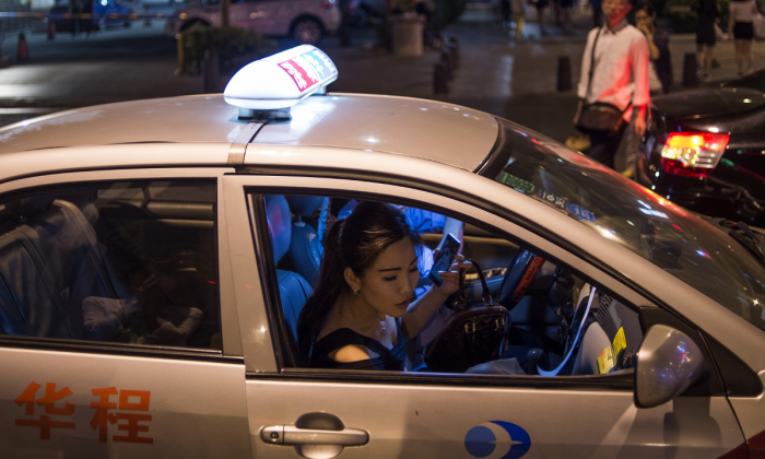 A woman exiting a taxi in China. (Fred Dufour/AFP/Getty Images)