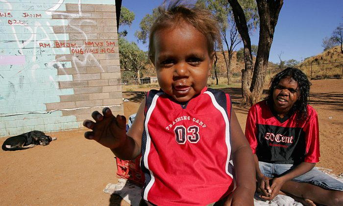 "Aboriginal 1 year old child Willy (L) and sister Lucia (R) play at the family's house in camp 'Hidden Valley' which is one of the ""town camps"" around Alice Springs on May 18, 2007. (ANOEK DE GROOT/AFP/Getty Images)"