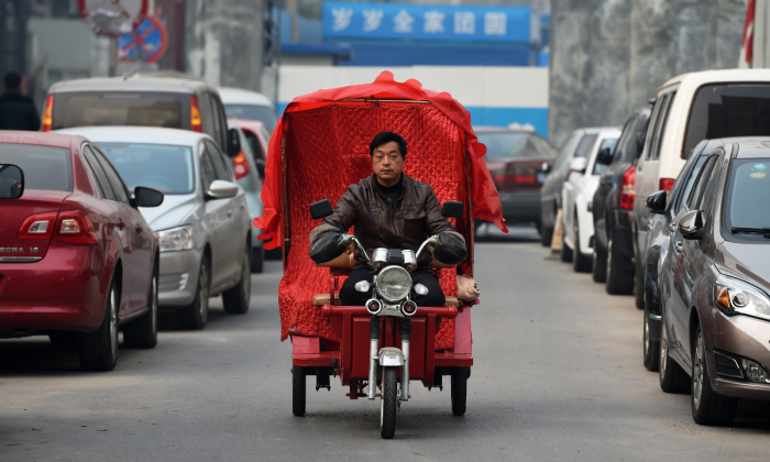 A man rides his covered electric tricycle taxi on a polluted day in Beijing on Nov. 26, 2014. (Greg Baker/AFP/Getty Images)