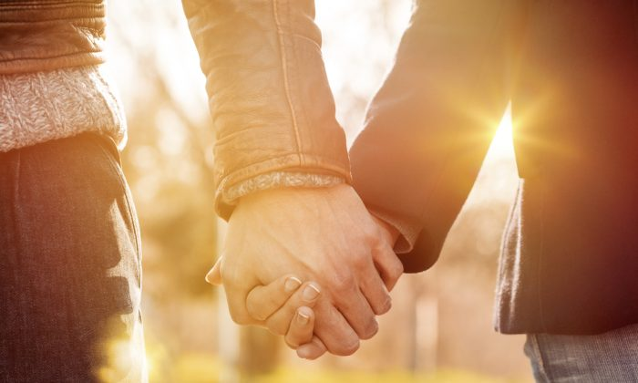 File photo of two people holding hands. (Ridofranz/iStock)