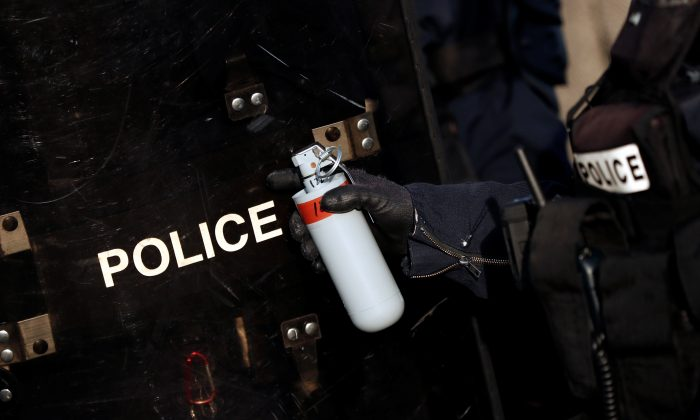 """A French riot police officer holds a tear gas grenade during a demonstration by the """"yellow vests"""" movement in Paris on Feb. 16, 2019. (Benoit Tessier/Reuters)"""