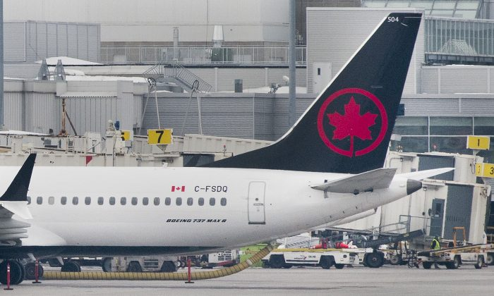 An Air Canada Boeing 737 Max 8 aircraft is shown next to a gate at Trudeau Airport in Montreal on March 13, 2019. Canada restricted Boeing 737 Max 8 aircrafts from its airspace on March 13. (The Canadian Press/Graham Hughes)