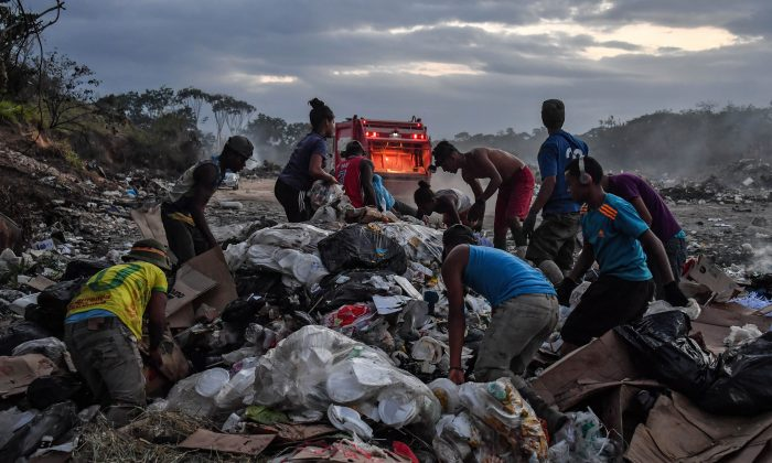 Venezuelan scavengers dig through trash at a landfill, in Pacaraima, Roraima State, Brazil, on the border with Venezuela, on February 28, 2019. NELSON ALMEIDA/AFP/Getty Images