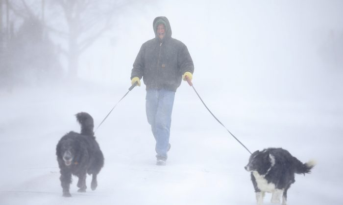 Tom Skaar of Cheyenne laughs while walking his dogs on House Avenue during a blizzard in Cheyenne, Wyo, on March 13, 2019. (Jacob Byk/The Wyoming Tribune Eagle via AP)