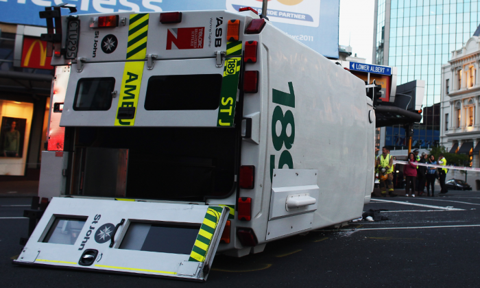 An ambulance lies on its side after colliding with a black Audi at the corner Custom St West and Lower Albert St in Auckland, New Zealand on Nov. 2, 2010. (Hannah Peters/Getty Images)