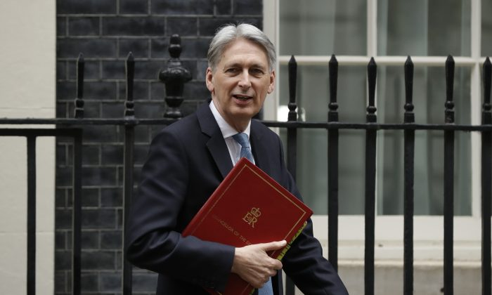 Finance Minister Philip Hammond leaves Downing Street to go to Parliament to deliver his Spring Statement in London on March 13, 2019. (Matt Dunham/AP Photo)