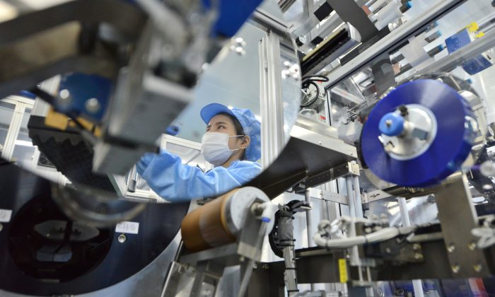 The reflection of a worker is seen at the production line of lithium-ion batteries for electric vehicles (EV) at a factory in Huzhou, Zhejiang province, China Aug. 28, 2018. Reuters/Stringer/File Photo