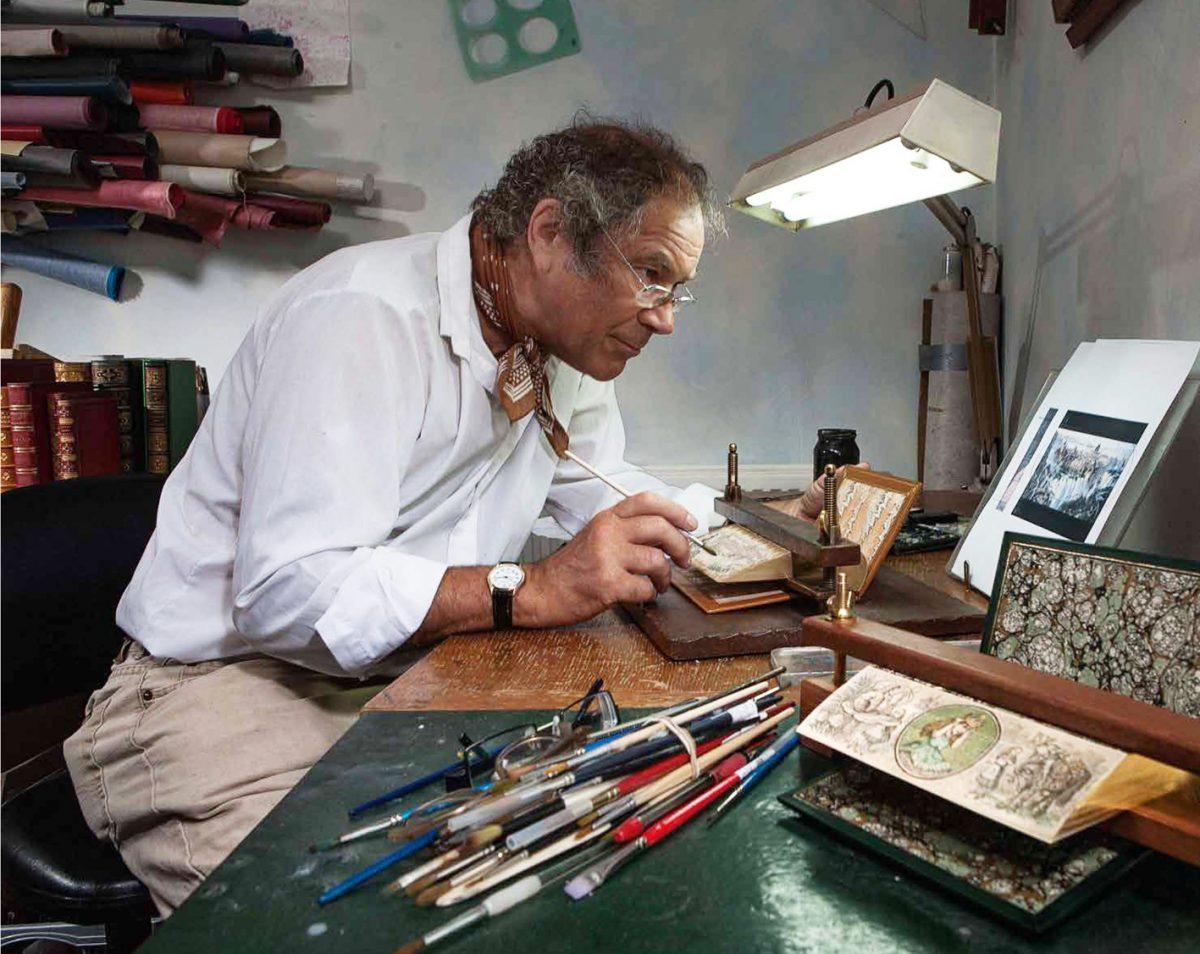 Man paints on books, artist.