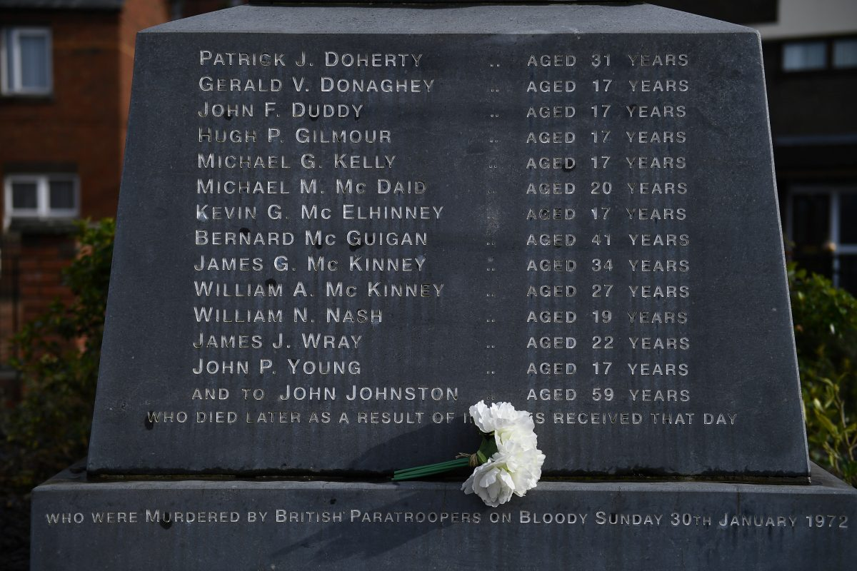 Flowers are left at the memorial for the people who died during the Bloody Sunday events