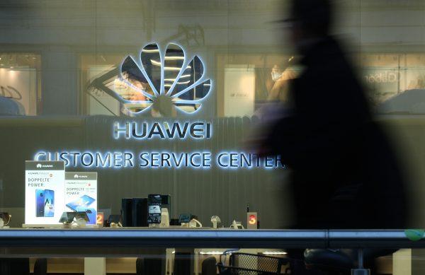 A man walks past a Huawei customer service center